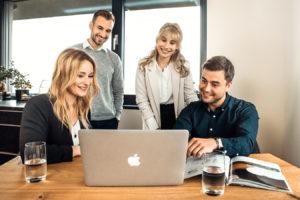 vier Angestellte schauen auf den Computer | Namox - Ihre Amazon SEO Agentur